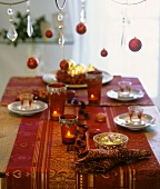 Laid table with Christmas decorations and tealights in glasses (in red)