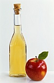 Bottle of cider apple vinegar with fresh apple