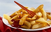 Chips with red plastic fork and ketchup on paper plate