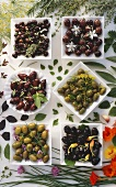 Various types of olives in dishes and fresh herbs