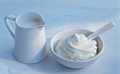 Small bowl of whipped cream and jug of cream