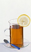 A glass of black tea with slice of lemon and spoon