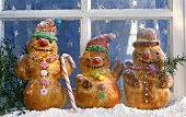 Baked snowmen (yeast dough) in front of a window