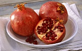 Two whole pomegranates and half a pomegranate in a dish