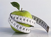 Green apple wrapped in tape measure
