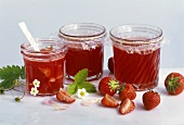 Three jars of strawberry jelly with rose petals