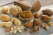 Assorted nuts, shelled and unshelled, on wooden background
