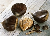 Three unshelled and one shelled sweet chestnut on wooden background