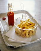 Chips in deep-frying basket with ketchup and salt