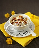Quark with dried fruit in a cup and saucer, floral decoration