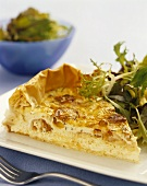 A piece of smoked salmon and Camembert quiche with salad leaves