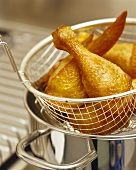 Deep-fried chicken drumsticks in a deep-frying basket