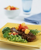 Beefsteak with mango and tomato salsa on salad leaves