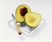 A halved avocado with knife on a glass plate