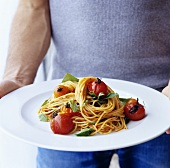 Man holding plate of spaghetti, cherry tomatoes and basil
