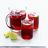 Cranberry juice with ice and lime in jug and two glasses