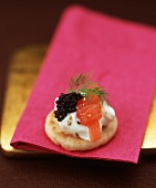 Small blini topped with creamed horseradish, smoked salmon and caviar