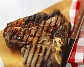 A grilled T-bone steak on a wooden board with a knife