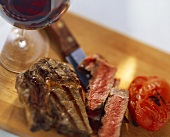 A grilled ribeye steak with tomatoes and red wine