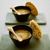 Two bowls of pumpkin soup with sesame bread