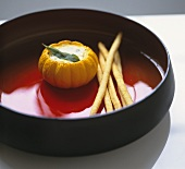 Baked mini pumpkin stuffed with cheese in a glass bowl