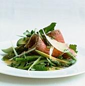 Slices of roast beef on an avocado-asparagus salad