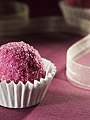 Chocolate coated in pink sugar in a paper case