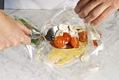 Putting tomatoes and mushrooms into a roasting bag