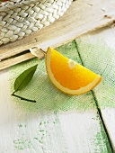 An orange wedge with a leaf