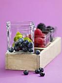 Blueberries, raspberries and blackberries in glass bowls