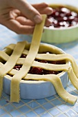 Lattice pastry being placed on a cherry tart