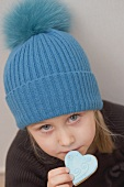 A little girl with a woolly hat eating a heart-shaped biscuit