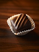 A chocolate praline in a praline case