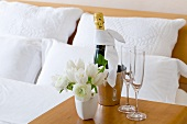 A bottle of champagne, glasses and a bunch of tulips on an occasional table in a hotel room