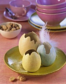 Easter decoration: three coloured eggshells with feather