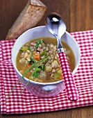 Hearty barley soup with vegetables and smoked bacon