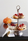 Small bread rolls with spread & cranberries on tiered stand