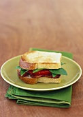 Fried bacon, tomato slices and basil in sandwich