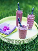 Three blueberry smoothies on a tray