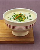 Light cream soup with julienne vegetables and fresh herbs
