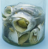 Several rollmops in a glass container