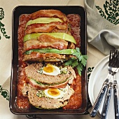 Spicy meatloaf with boiled eggs on tomato sauce