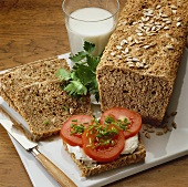 Wholemeal bread with herbs, one slice topped with tomato