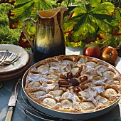 Apple cake with plums in round baking tin