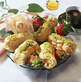 Filled éclairs and strawberries with ground pistachios