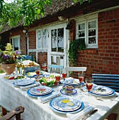 Laid table with food in front of house in country