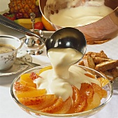 Zabaglione (whipped wine cream) being poured over orange segments