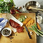 Meat, vegetables, pumpkin seeds etc. on a kitchen board