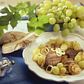 Fried poultry livers with onions and grapes