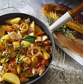 Pan-cooked fish, potatoes, tomatoes and bacon